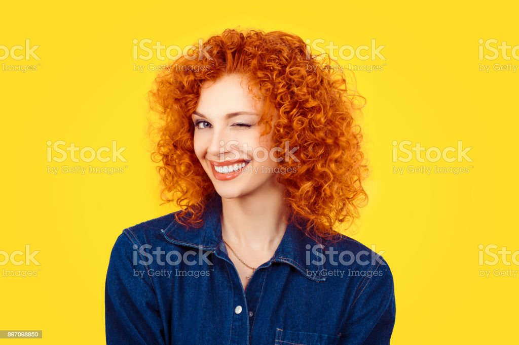 Winking. Closeup woman redhead curly hair smiling blinking eye to you camera isolated on yellow background. Happy life pictures, happiness stock photo