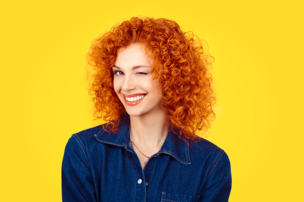 Winking. Closeup woman redhead curly hair smiling blinking eye to you camera isolated on yellow background. Happy life pictures, happiness Winking. Closeup woman redhead curly hair smiling blinking eye to you camera isolated on yellow background. Happy life pictures, happiness blinking stock pictures, royalty-free photos & images