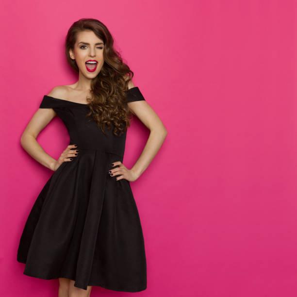 Winking Woman In Elegant Black Dress Cocktail Dress stock photo