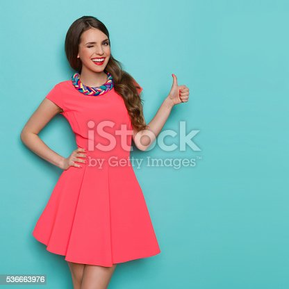 Smiling beautiful young woman in pink mini dress showing thumb up and winking. Three quarter length studio shot on turquoise background.