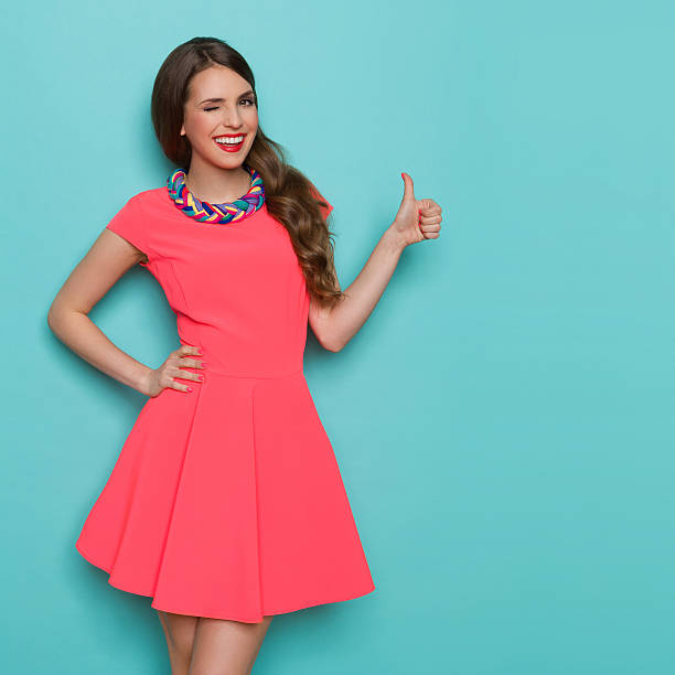 winking woman showing thumb up - mini dress stock photos and pictures