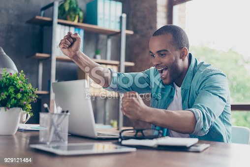 istock Winner! A dream of the young afro american entrepreneur came true. He is very excited, wearing smart casual, celebrating in the office 929121484