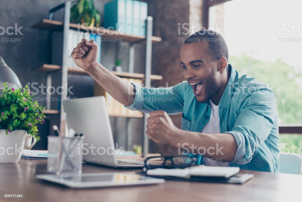 Winner! A dream of the young afro american entrepreneur came true. He is very excited, wearing smart casual, celebrating in the office stock photo