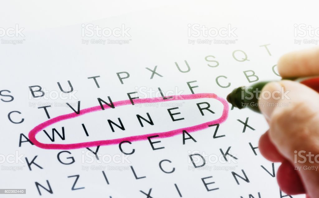 'Winner' being circled in red on page of jumbled letters stock photo