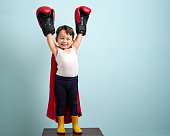 3-4 years old winner boy wearing boxing gloves is raising his hands up to show his success and victory.
