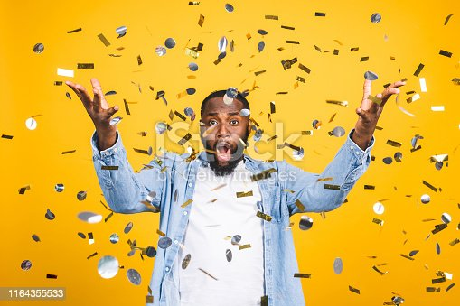 Winner! Cheerful african american young man dancing over yellow background.