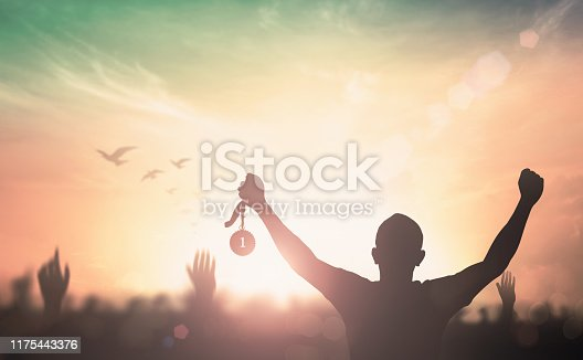 Silhouette champion hand holding gold medal reward against blurred sport crowd autumn sunset background