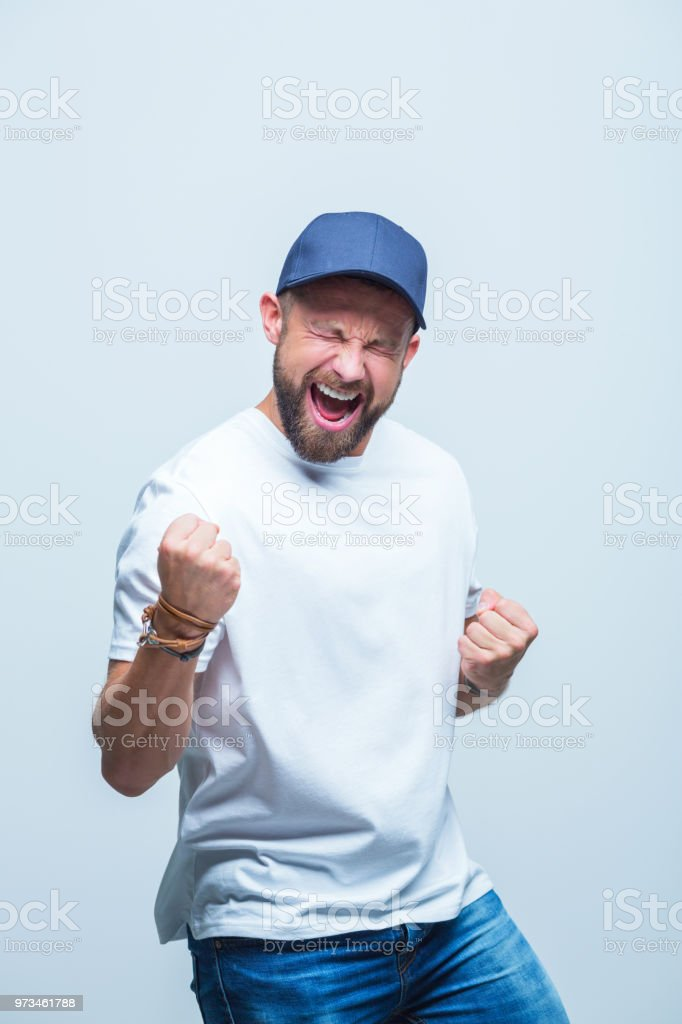 Winner - excited caucasian man Portrait of happy man standing with clenched fists and screaming, man celebrating the success. Adult Stock Photo