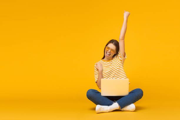 vencedor! a menina de sorriso excited que senta-se no assoalho com portátil, levantando uma mão no ar é ela ganha, isolada no fundo amarelo - excitação - fotografias e filmes do acervo