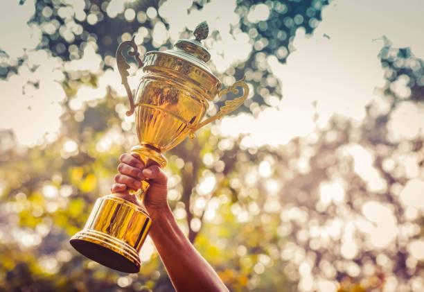 Winner holding golden trophy stock photo