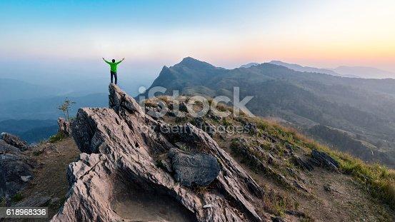 istock Winner man on peak of rocks mountain Hike at sunset 618968336