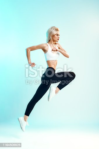Winner. Side view of sporty young woman in white top and black leggings jumping against blue background in studio. Sport. Active lifestyle. Studio shot