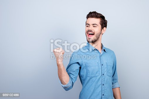 istock Winner! Young handsome man is celebrating victory. He is raising up fist and screaming 939102486