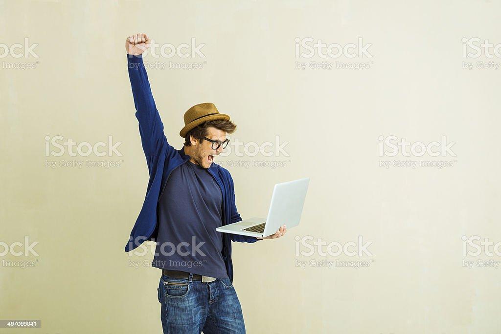 Winner young man using laptop stock photo
