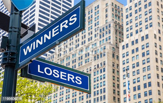 Winners losers crossroads street sign, blue color road sign. Win, lose choice decision concept. Highrise buildings background,