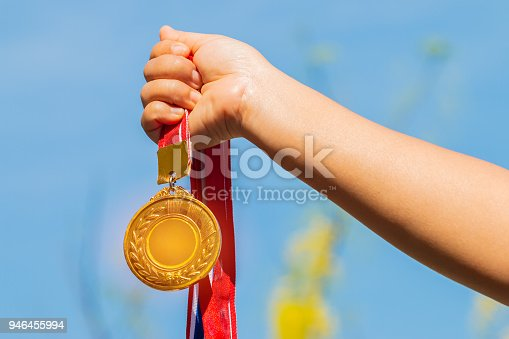 istock Winners success award concept : Champion hand holding gold medals reward against blue sky background. Winning at sport games show success. 946455994