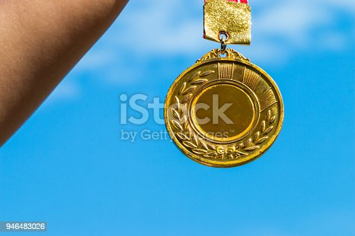 istock Winners success award concept : Champion hand holding gold medals reward against blue sky background. Winning at sport games show success. 946483026