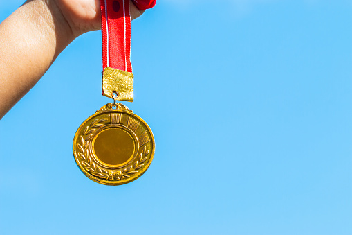istock Winners success award concept : Champion hand holding gold medals reward against blue sky background. Winning at sport games show success. 950351328