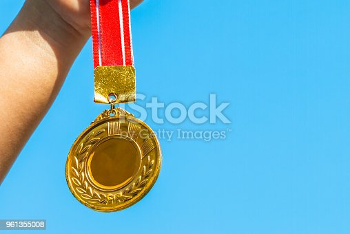 istock Winners success award concept : Champion hand holding gold medals reward against blue sky background. Winning at sport games show success. 961355008