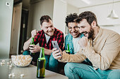 Three friends are at home watching sport match live on their smart phone