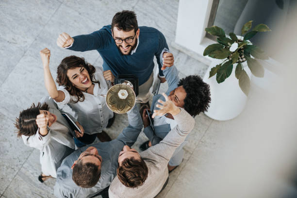 Winning a trophy for business achievement! Above view of happy business team celebrating winning a trophy for their achievement. trophy award stock pictures, royalty-free photos & images