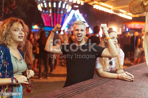 Group of young happy friends having fun while celebrating winning a prize in knockdown game at amusement park
