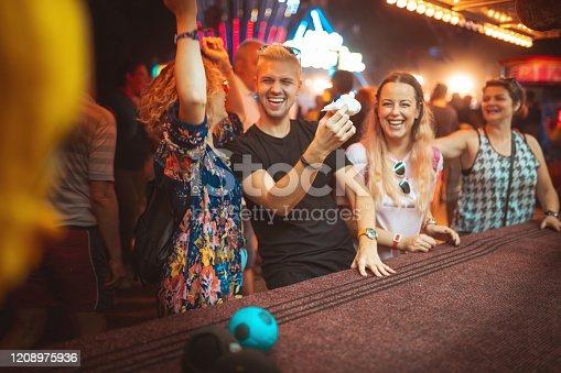 Friends having fun on knockdown game, winning toy plane, amusement park in background