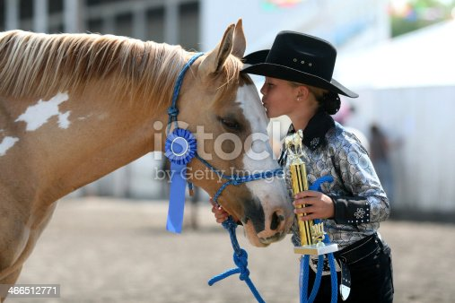 cowgirl contestant holding her ribbons she won with her horse in an arena during fair