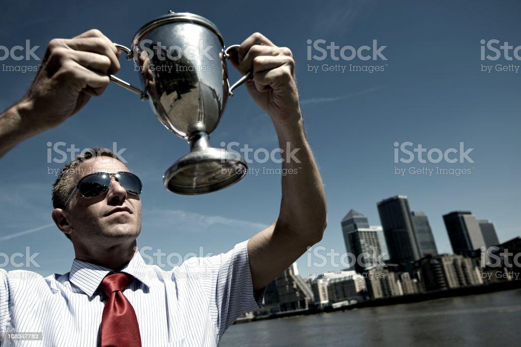 Winning Businessman Holding Silver Trophy above Skyline royalty-free stock photo