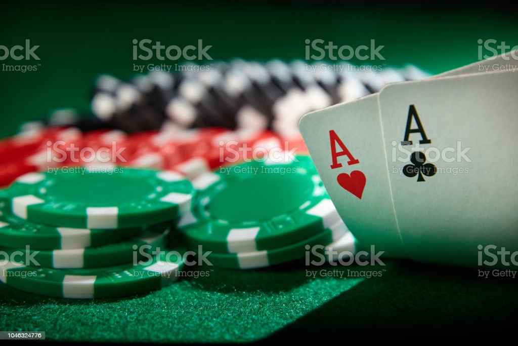 A pair of aces and gambling chips on green table.