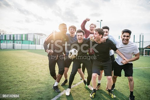 Group of young man hugging and celebrating soccer match success