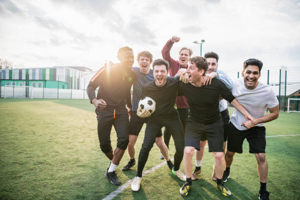 Winning football team cheering Group of young man hugging and celebrating soccer match success leisure equipment stock pictures, royalty-free photos & images