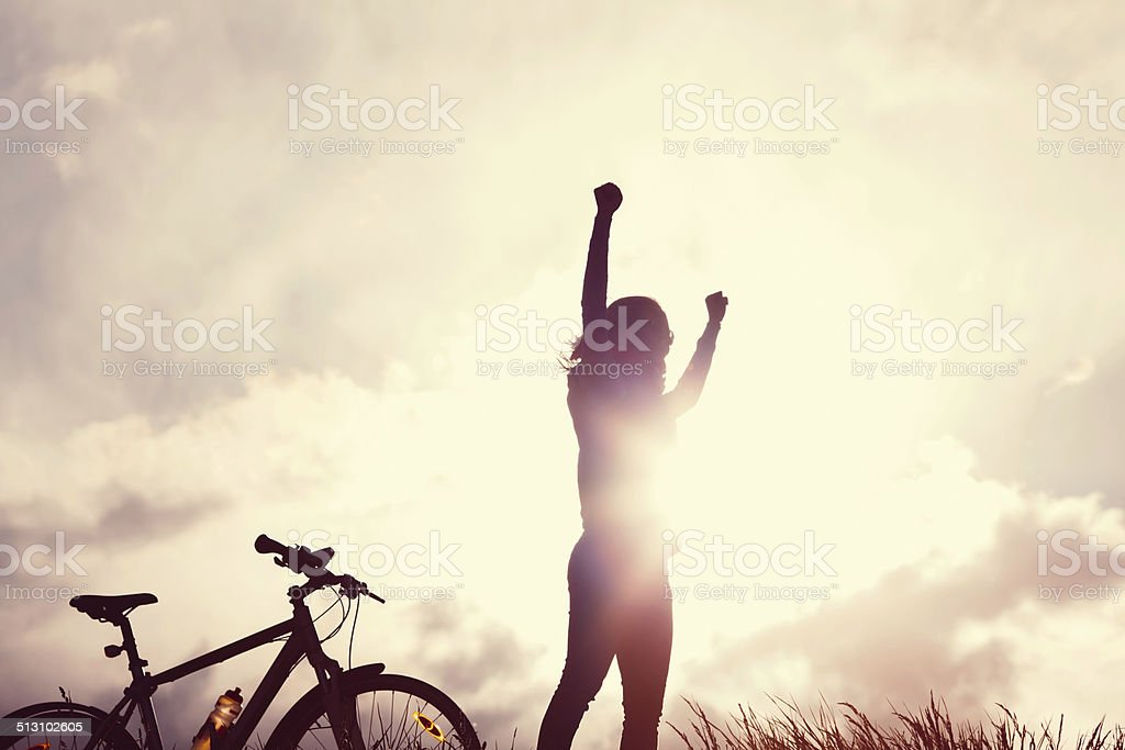 Winning girl with bike silhouette stock photo