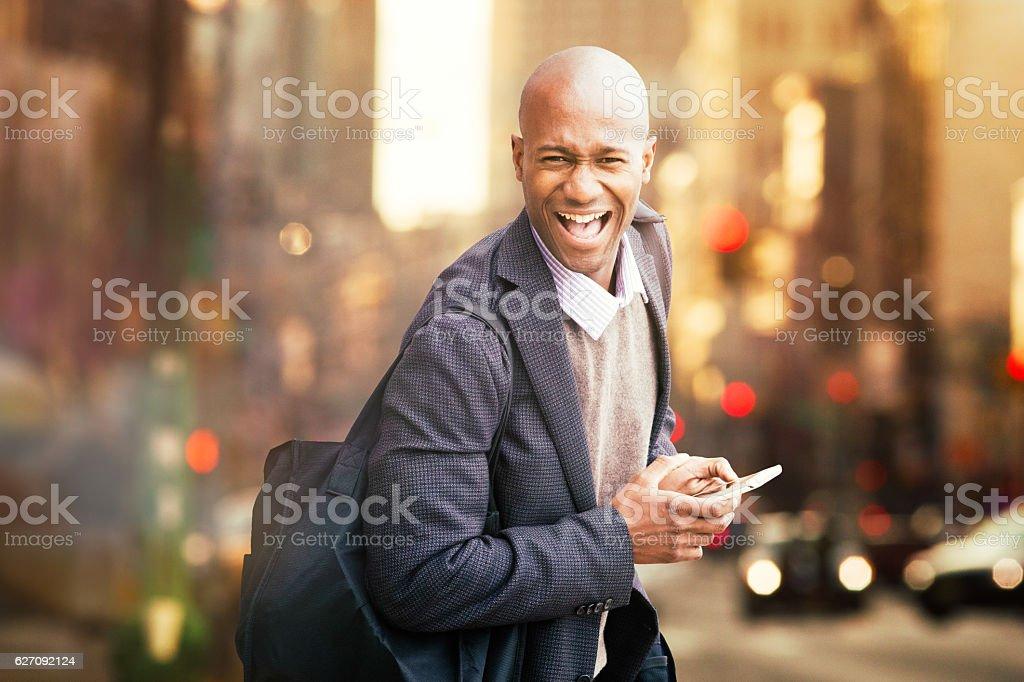 Winning happy black man urban portrait with phone stock photo