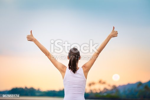 Young woman with arms in the air giving thumbs up.