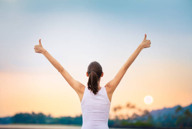 Winning, success  and life goals concept. Young woman with arms in the air giving thumbs up. wellbeing stock pictures, royalty-free photos & images