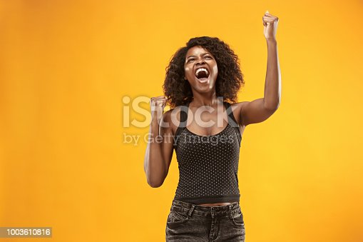 istock Winning success woman happy ecstatic celebrating being a winner. Dynamic energetic image of female afro model 1003610816