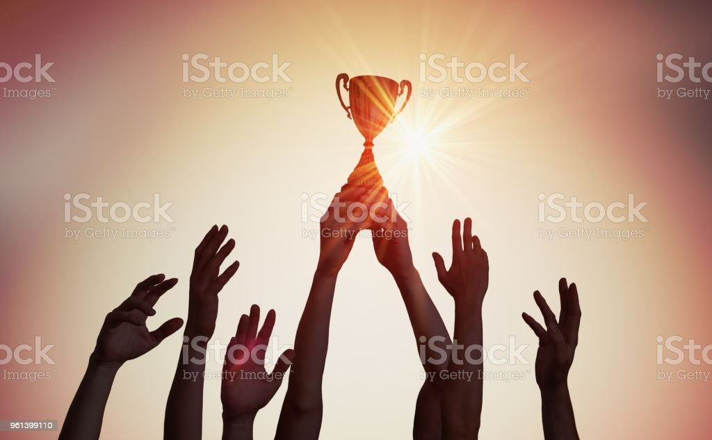 Winning team is holding trophy in hands. Silhouettes of many hands in sunset. stock photo