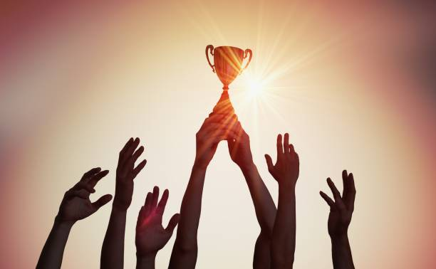 winning team is holding trophy in hands. silhouettes of many hands in sunset. - trophy award stock photos and pictures