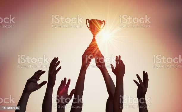 Winning Team Is Holding Trophy In Hands Silhouettes Of Many Hands In Sunset - Fotografias de stock e mais imagens de Alcançar