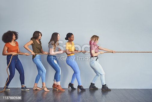Studio shot of a group of young women playing tug of war against a gray background