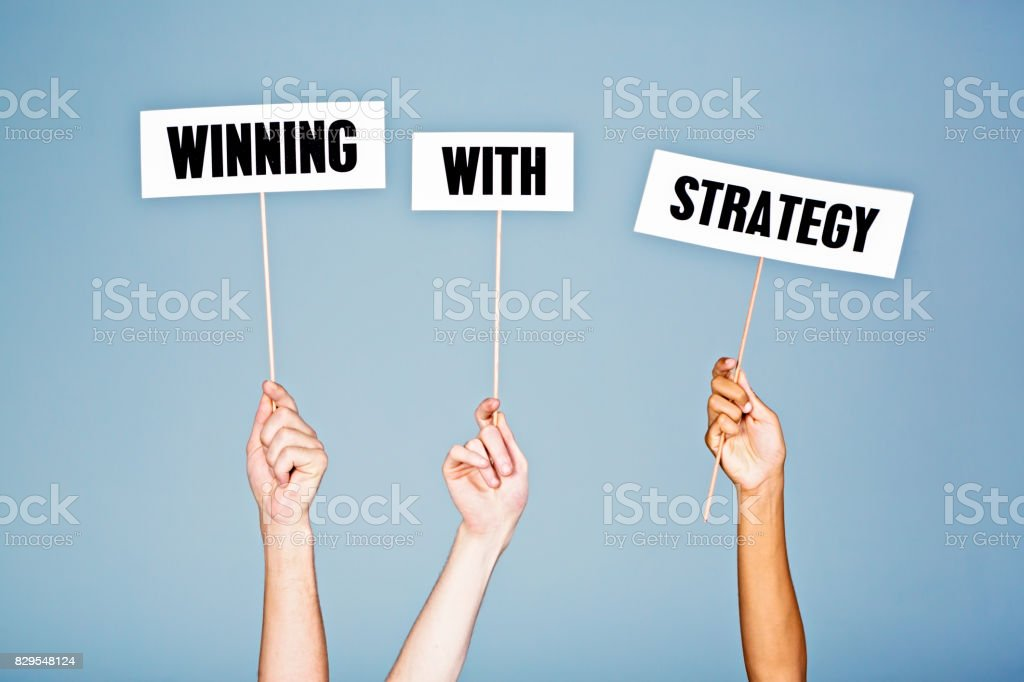 'Winning with strategy' say hand-held signs stock photo
