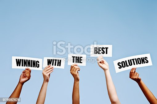Hand-held signs read 'Winning with the best solutions'.