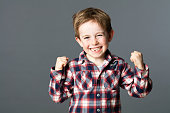 winning young child with tooth missing raising arms for excitement
