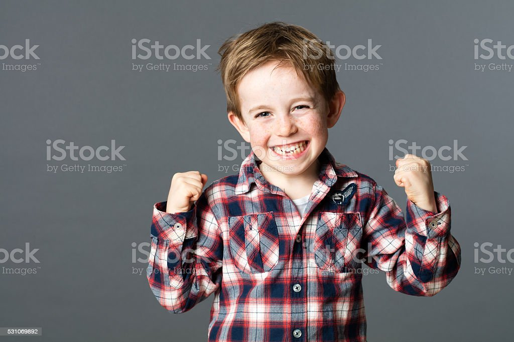 winning young child with tooth missing raising arms for excitement stock photo