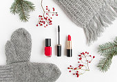 Winter accessories, cosmetics and clothes on white background. Flat lay