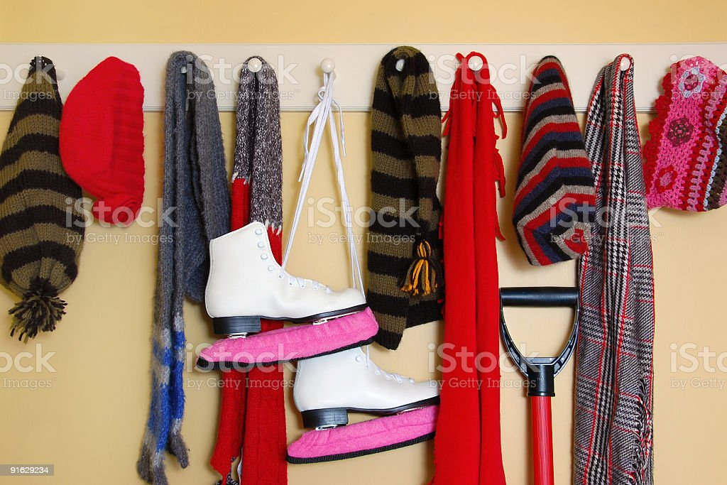 Winter attire and ice skates hang on clothes rack stock photo