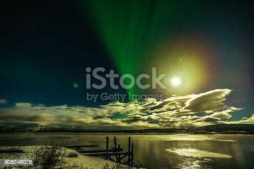 Winter: Spectacular Aurora Borealis, (the Northern Lights) appear with the Moon Rise over Lake Torneträsk in Swedish Lapland, Arctic Circle