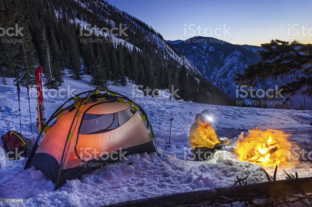 Winter Backcountry Camp with Man Cooking on Gas Stove royalty-free stock photo