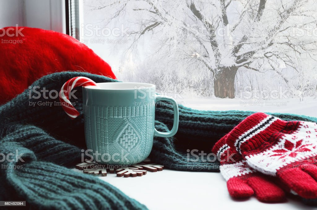 Winter background - cup, candy cane, woolen scarf and gloves stock photo